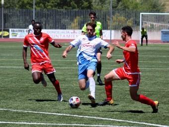 Paco Ariza avanza con el balón entre dos jugadores motrileños. FOTO: MIGUEL JÁIMEZ.