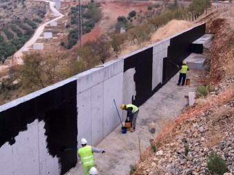 Operarios trabajando en la impermeabilización de un muro cerca de la Venta del Rayo.