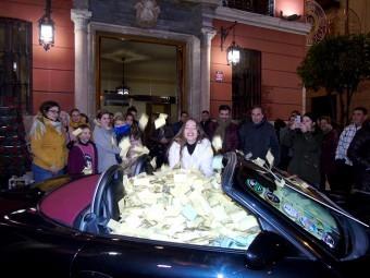Laura lanzando las papeletas al aire para extraer la ganadora ante el público asistente. FOTO: J.M.J