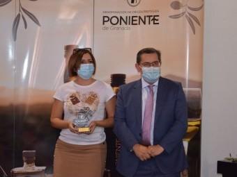 Una representante de la cooperativa recibe el premio de manos del presidente de la Diputación