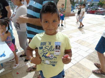 Un niño luce las diferentes chapas con banderas y el eslogan del proyecto