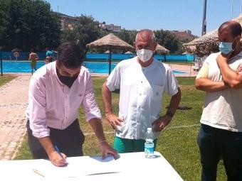 El alcade firma en presencia del representante del Centro de Salud y del concejal de Salud. FOTO: J.